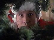 Chevy Chase as Clark Griswold peeking through the branches of a Christmas tree in National Lampoon's Christmas Vacation.