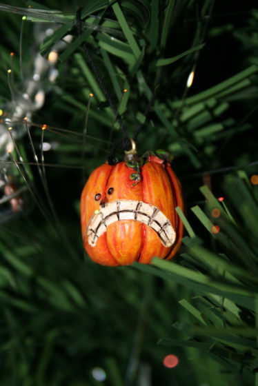A pumpkin ornament on a Halloween tree.