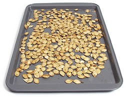 A cookie sheet filled with leftover pumpkin seeds.